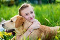 Flickan kramar hunden Royaltyfri Bild