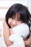 Flickan kramar nallen Arkivbild
