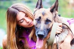 Flickan kysser en herde härlig hundkvinna Arkivfoto