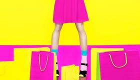 Flickan lägger benen på ryggen färgrik galen shopping Arkivfoton
