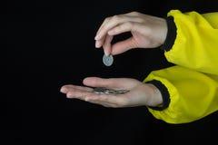 Flickan lägger myntet i handen, närbilden, svart bakgrund, guling royaltyfri fotografi