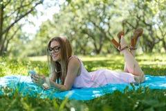 Flickan lägger ner eller koppla av på lyssnande musik för grönt gräs med smartphonen i sommar eller fjädrar Fotografering för Bildbyråer
