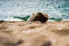 Flickan lägger på sanden vid havet royaltyfri fotografi