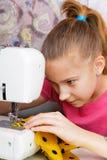 Flickan lär att sy arkivbild
