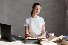 Flickan lär från böcker på tabellen arkivbild