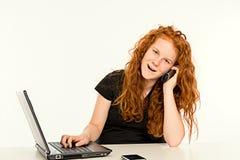 Flickan lär med datoren och kalla Royaltyfri Foto