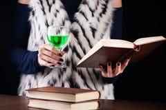 Flickan läser boken och dricker absint eller den gröna felika drinken arkivfoto