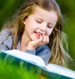 Flickan läser boken som ligger på det gröna gräset arkivbild