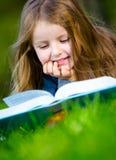 Flickan läser boken som ligger på gräset royaltyfria bilder