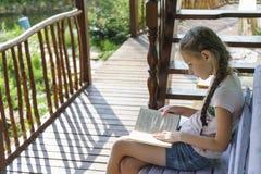Flickan läser en bok i landet på en bänk arkivbild