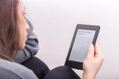 Flickan läser en bok med en eBookavläsare Royaltyfri Bild
