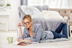 Flickan läser en bok på golvet royaltyfria bilder
