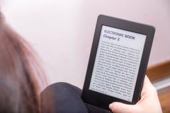 Flickan läser en roman med en eBookavläsare Royaltyfri Fotografi