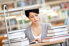 Flickan läser på den läs- korridoren arkivbilder