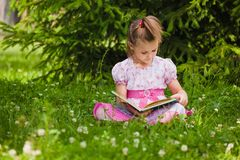 Flickan läser på gräset royaltyfria foton
