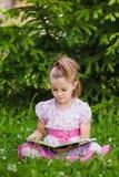 Flickan läser på gräset arkivfoton