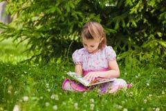 Flickan läser på gräset arkivbild