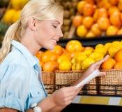 Flickan läser shoppinglistan nära högen av frukter royaltyfri bild