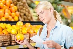 Flickan läser shoppinglistan och räcker en apelsin royaltyfria bilder