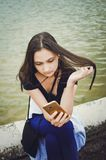 Flickan l?ser sms i smartphonen, livsstil royaltyfri foto