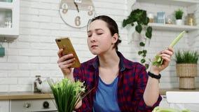 Flickan läser sms på telefonleenden äter selleri i ljust kök stock video