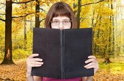 Flickan läser stora bok- och höstträn Arkivfoto