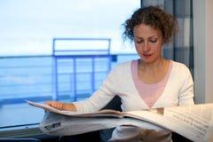 Flickan läste tidningen i kabin av den stora shipen royaltyfri fotografi