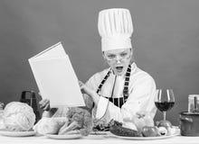 Flickan l?ste b?sta kulinariska recept f?r bok Kulinariskt utbildningsbegrepp Kvinnlign i hatt och f?rkl?de vet allt omkring arkivbild