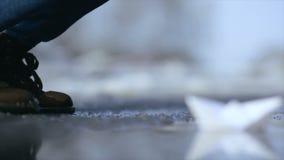 Flickan lanserar ett pappers- fartyg i en pöl stock video