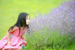 Flickan ler blommor Fotografering för Bildbyråer