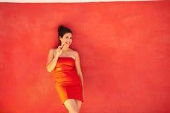 Flickan ler elektronisk cigarettE-Cig benägenhet på röd bakgrund Arkivfoto
