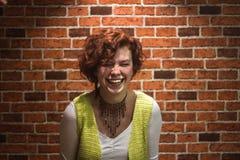 Flickan ler med ljust rödbrun lockigt hår och får fräknar royaltyfria bilder
