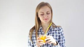 Flickan ler och dricker orange fruktsaft till och med ett sugrör arkivfilmer