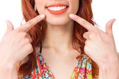 Flickan ler och punkter med hennes fingrar till hennes kant Rödhårig manflicka arkivbild