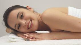 Flickan ler på massagetabellen royaltyfri fotografi