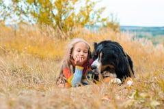 flickan ligger bredvid den stora hunden Berner Sennenhund royaltyfri bild