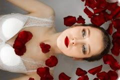Flickan ligger i badrummet med rosa kronblad Ett wellnessbad med rosor arkivfoto