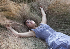 Flickan ligger i ett gräs Arkivfoto