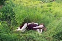 Flickan ligger i gräset Royaltyfria Bilder