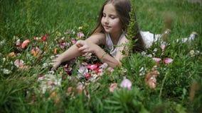 Flickan ligger i gräset och ser doftflaskorna lager videofilmer