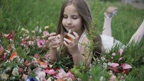 Flickan ligger i gräset och ser doftflaskorna stock video