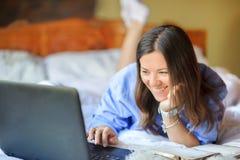 Flickan ligger i säng och arbetar bak en bärbar dator arkivfoton