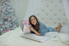 Flickan ligger i säng och jublar med en julklapp i henne händer och ett träd för nytt år i ett vitt rum arkivbild