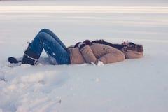 Flickan ligger i snön royaltyfri fotografi