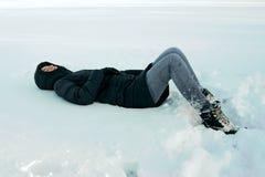 Flickan ligger i snön arkivbild