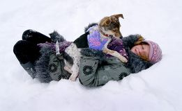Flickan ligger i snön med hennes favorit- hund Vinterentertai royaltyfri bild