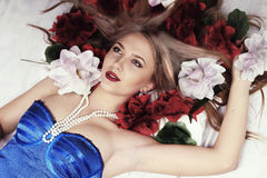 Flickan ligger i säng som omges av blommor Royaltyfri Fotografi