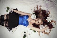 Flickan ligger i säng som omges av blommor Fotografering för Bildbyråer
