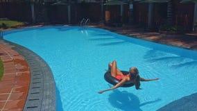 Flickan ligger på cirkeln som solbadar i pöl stock video