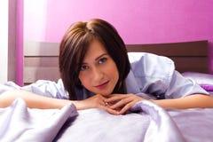 Flickan ligger på en säng till tittaren Arkivfoto